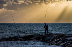 Surfcaster i solnedgången Royaltyfri Bild
