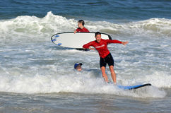 Surfeing lession in Gold Coast Queensland Australia. GOLD COAST, AUS - NOV 01 2014:Female wave surfing instructor teaches man and woman how to surf in Surfers Stock Photography