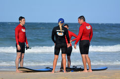 Surfeing lession in Gold Coast Queensland Australia. GOLD COAST, AUS - NOV 01 2014:Female wave surfing instructor teaches men and women how to surf in Surfers Royalty Free Stock Photography
