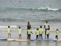 Surfen Sie Schule mit Kindern und Lehrern auf dem Strand Lizenzfreie Stockfotografie