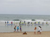 Surfen Sie Schule mit Kindern und Lehrern auf dem Strand Stockbild