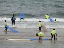 Surfen Sie Schule mit Kindern und Lehrern auf dem Strand Stockfotografie