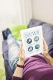 Surfend Internet en het lezen van nieuws met digitale tablet Stock Afbeeldingen