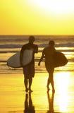 Surfende Paare auf kuta Strand lizenzfreie stockbilder