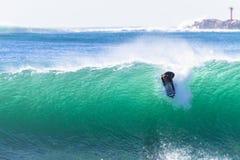 Surfende Surfer-Fahrgroße Welle Stockfotos