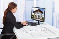 Surfendes Haus des weiblichen Architekten auf Computer am Schreibtisch Stockbild