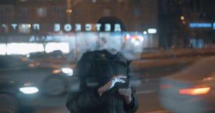 Surfendes Internet der jungen Frau auf Auflage, wenn auf Bus in der Abendstadt gewartet wird stock footage