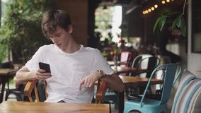 Surfendes Internet des jungen Mannes im Handy, handliche Note und senden Textnachricht im Café Hübscher Jugendlicher, der herein  stock footage