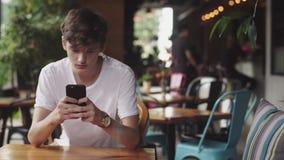 Surfendes Internet des jungen Mannes im Handy, handliche Note und senden Textnachricht im Café Hübscher Jugendlicher, der herein  stock video footage