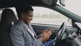 Surfendes Social Media des glücklichen Afroamerikanergeschäftsmannes auf seinem Tablet-Computer, der innerhalb seines Autos sitzt Stockbild