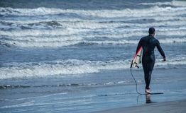 Surfer και ο πίνακάς του Στοκ εικόνα με δικαίωμα ελεύθερης χρήσης