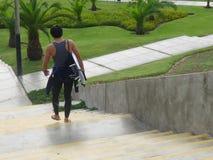 Surfer με την ιστιοσανίδα του που πηγαίνει στην παραλία στη Λίμα στοκ εικόνες
