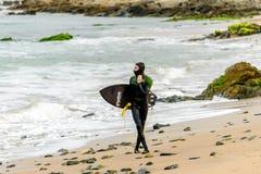 Surfer με τον κάνοντας σερφ πίνακα Στοκ Φωτογραφίες