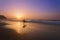 Surfer που εισάγει το νερό στο ηλιοβασίλεμα Στοκ Εικόνες