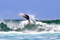 Surfer που κάνει σερφ τα κύματα Στοκ Φωτογραφίες