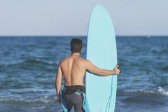 Surfer που κρατά την μπλε ιστιοσανίδα του Στοκ εικόνες με δικαίωμα ελεύθερης χρήσης