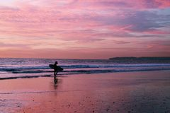 Surfer στην παραλία κατά τη διάρκεια του ηλιοβασιλέματος στοκ εικόνες με δικαίωμα ελεύθερης χρήσης