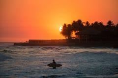 Surfer στο νερό κατά τη διάρκεια ενός ηλιοβασιλέματος σε Playa EL Tunco, EL Salvad Στοκ Φωτογραφίες
