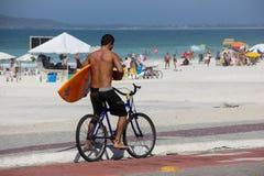 Surfer στο ποδήλατο στην ηλιόλουστη ημέρα Στοκ εικόνα με δικαίωμα ελεύθερης χρήσης