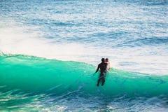 Surfer στο υγρό κοστούμι και το μπλε ωκεάνιο κύμα Σερφ στον μπλε ωκεανό Στοκ Φωτογραφία