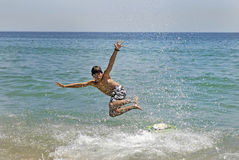 Surfer. Boy jumping in the air with skimboard in the sea Stock Images