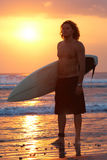 Surfer. Portrait of young man standing on seashore with windsurf board at sunset Royalty Free Stock Image