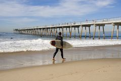 Surfer 3. A young man is walking along the beach ready to go surfing Royalty Free Stock Images