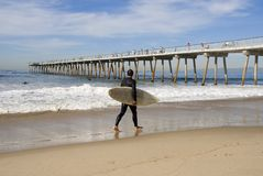 Surfer 3. A young man is walking along the beach ready to go surfing Stock Image