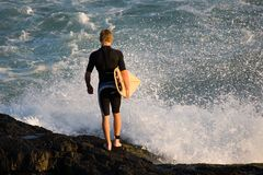 Surfer. A young male surfer with surfboard under his arm, about to enter the water, early morning Stock Images