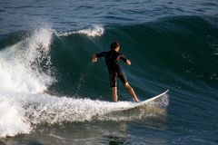 Surfer. A young male surfer catching a wave Royalty Free Stock Image
