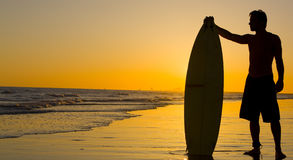 Surfer. A silhouette of a surfer at sunset Stock Image