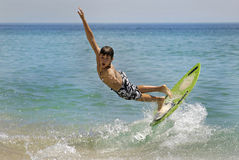 Surfer. Boy jumping in the air with skimboard in the sea Stock Photo