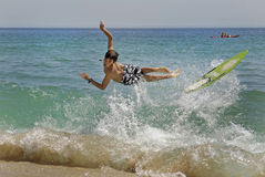 Surfer. Boy jumping in the air with skimboard in the sea Royalty Free Stock Photography