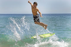 Surfer. Boy jumping in the air with skimboard in the sea Stock Image