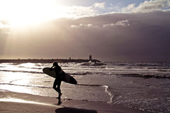 Surfer along the beach at sunset Royalty Free Stock Photo