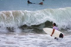 Surfer auf blauem Ozean nahe großer Welle, Bali, Brandungsstelle stockfotografie