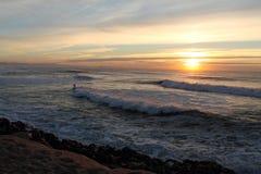 Surfer auf brechender Welle in der bunten Landschaft von Atlantik mit Gebirgsla rhune im Sonnenuntergang Lizenzfreie Stockfotografie