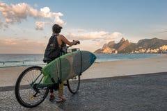 Surfer auf einem Fahrrad am Strand Lizenzfreie Stockfotografie