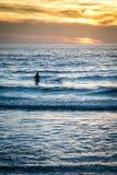 Surfer auf Strandsonnenuntergang auf Strand und Wellen Stockbilder
