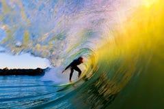 Surfer auf Welle am Sonnenuntergang lizenzfreie stockbilder