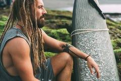 Surfer avec des dreadlocks et tatoos avec le surfingboard image stock