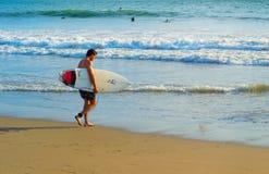 Surfer avec la planche de surf à la plage Photographie stock libre de droits