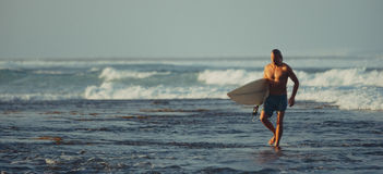 Surfer avec la planche de surf sur un littoral de Sumbawa, Indonésie Photographie stock libre de droits