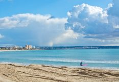 Surfer avec le conseil rose sur la plage d'hiver Photographie stock