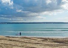 Surfer avec le conseil rose sur la plage d'hiver Photos stock