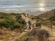 Surfer avec son panneau de ressac descendant la falaise à la plage pendant le coucher du soleil images stock
