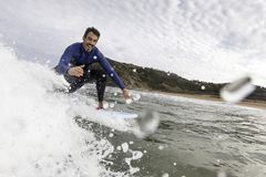 Surfer ayant l'amusement attrapant une vague et la saluant photos stock