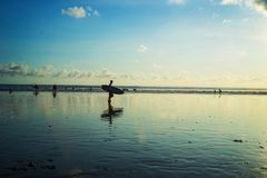 Surfer back home at Kuta Beach, Bali-Indonesia in the sunset time stock image