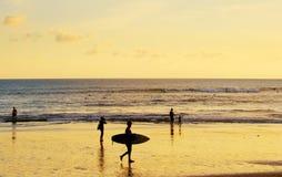 Surfer at Bali island beach. Surfer walking on a Bali island beach at sunset. Indonesia stock photography