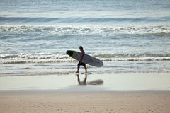 A surfer on the beach in Durban Stock Photography